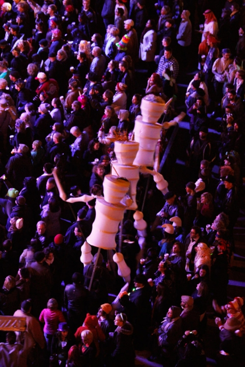Large figures walk through the crowds.